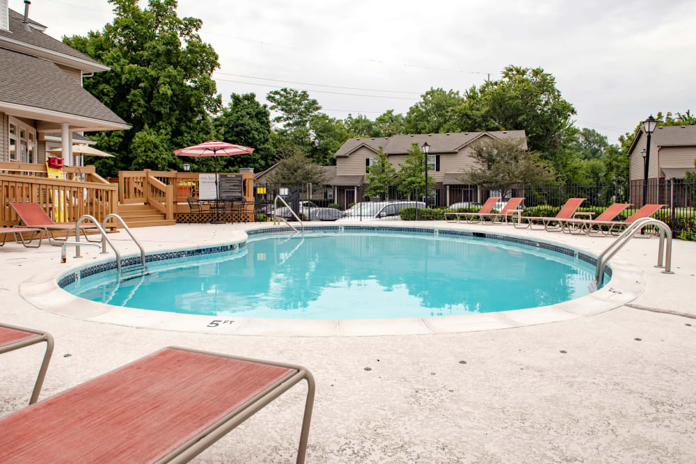 Sparkling swimming pool surrounded by chaise lounges and shaded seating at Cooper Creek in Louisville, Kentucky