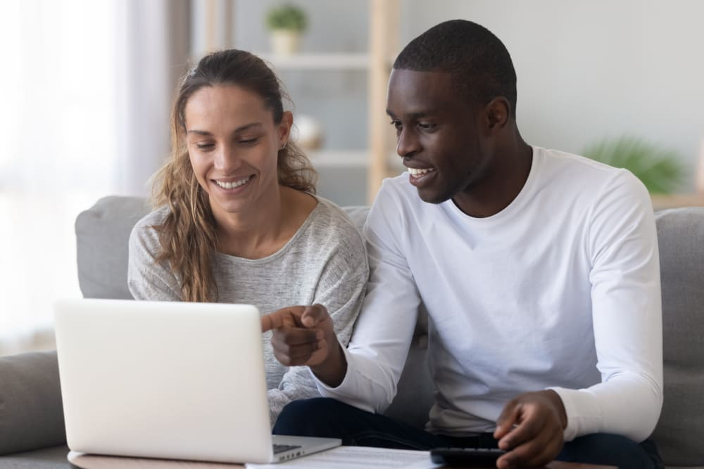 Couple looking at their computer together at Kiwi Goji Apartments in Memphis, Tennessee