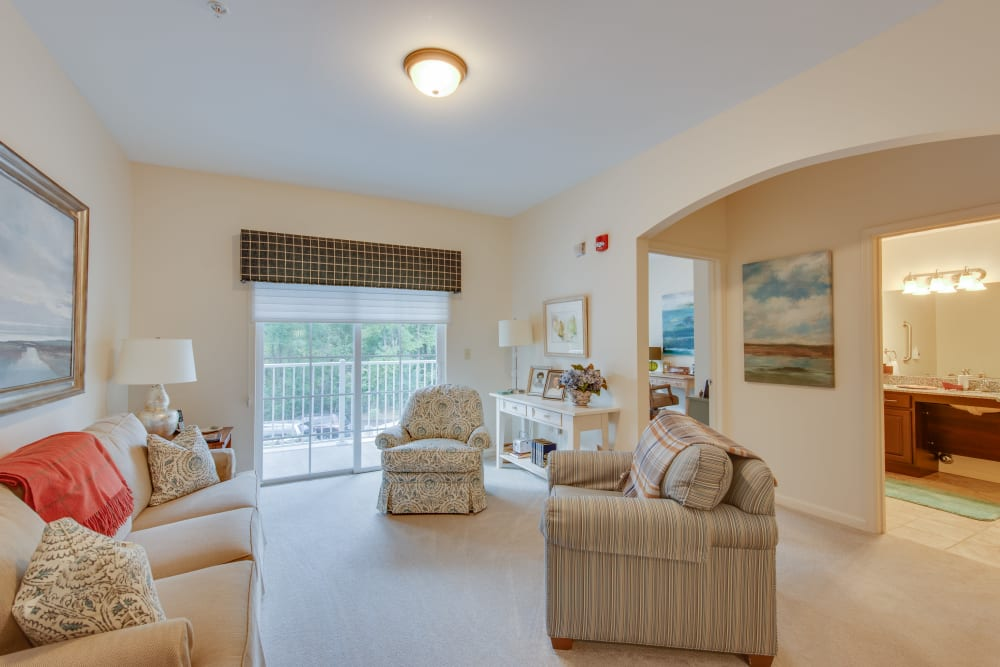An apartment living room with doors to the balcony at Harmony at Harbour View in Suffolk, Virginia
