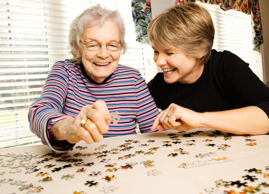 Working a puzzle with a family member at Prairie House Assisted Living and Memory Care in Broken Arrow, OK