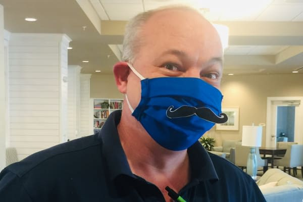 A staff member with a mustache on his mask at Merrill Gardens.