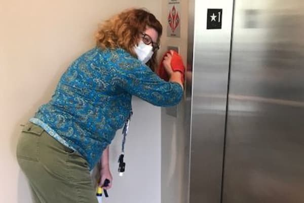 A staff member cleaning the elevator at Merrill Gardens.