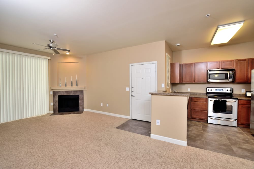 Open-concept floor plan showcasing fireplace and modern kitchen in apartment home at Lumiere Chandler in Chandler, AZ
