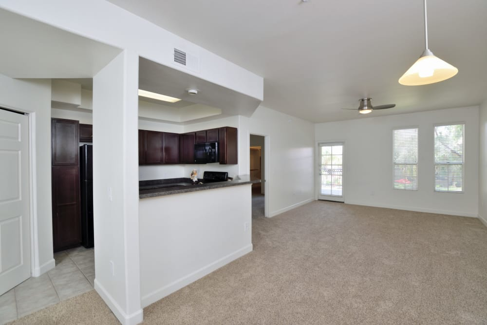 Large, open living room with modern kitchen in the background in apartment home at Lumiere Chandler in Chandler, AZ