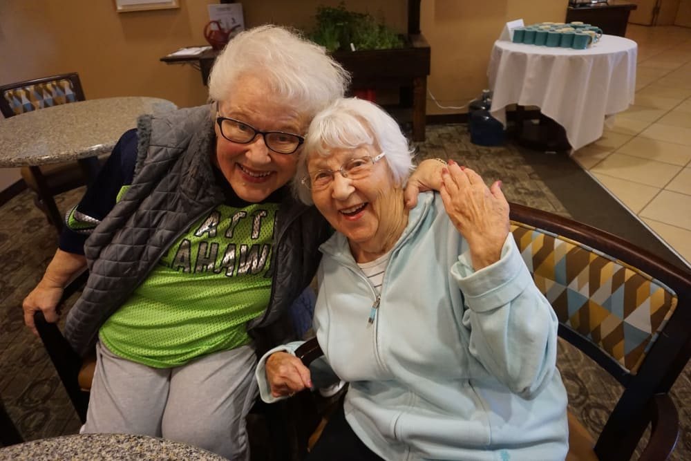 Two residents hugging at Merrill Gardens at Kirkland in Kirkland, WA
