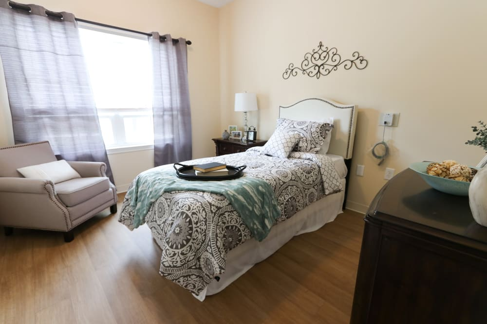 A furnished bedroom with wood flooring at The Harmony Collection at Roanoke - Memory Care in Roanoke, Virginia
