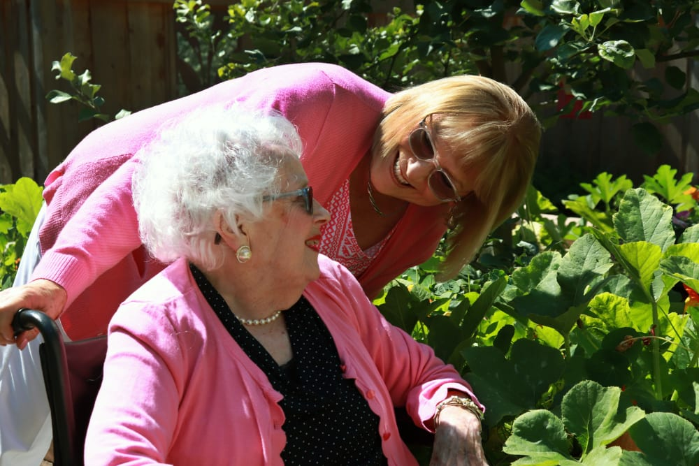 Resident and caregiver enjoying a stroll through the garden at The Springs at Carman Oaks in Lake Oswego, Oregon.