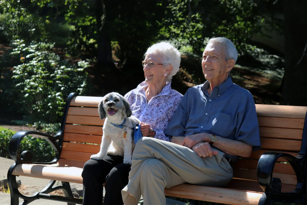 A resident couple sitting in the garden with their dog at The Springs at Carman Oaks in Lake Oswego, Oregon.