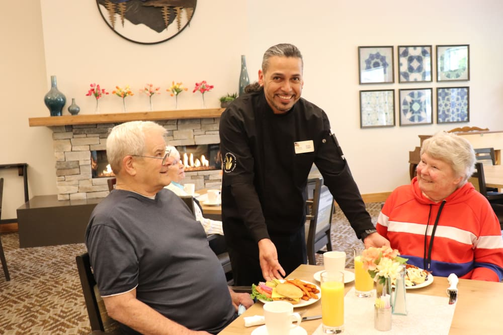 Residents being served a meal by chef at The Springs at Clackamas Woods in Milwaukie, Oregon.