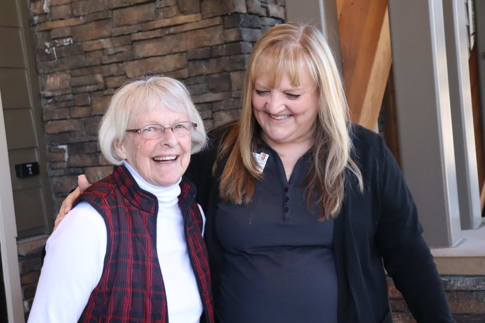 Resident smiling with caregiver at The Springs at Greer Gardens in Eugene, Oregon.