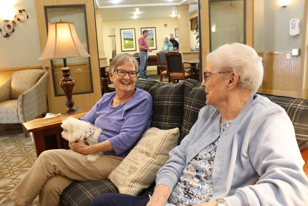 Residents chatting in the lounge area while one holds their little dog at The Springs at Sunnyview in Salem, Oregon