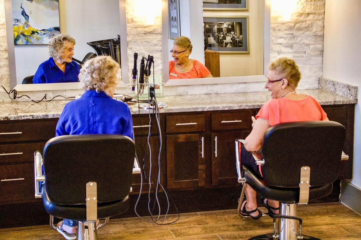 A couple seniors enjoying the salon at The Landing at Stone Oak in San Antonio, Texas