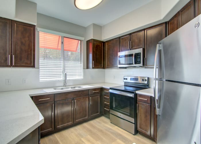 Beautifully renovated gourmet kitchen with stainless-steel appliances and granite countertops in an apartment home at The Residences at Stadium Village in Surprise, Arizona