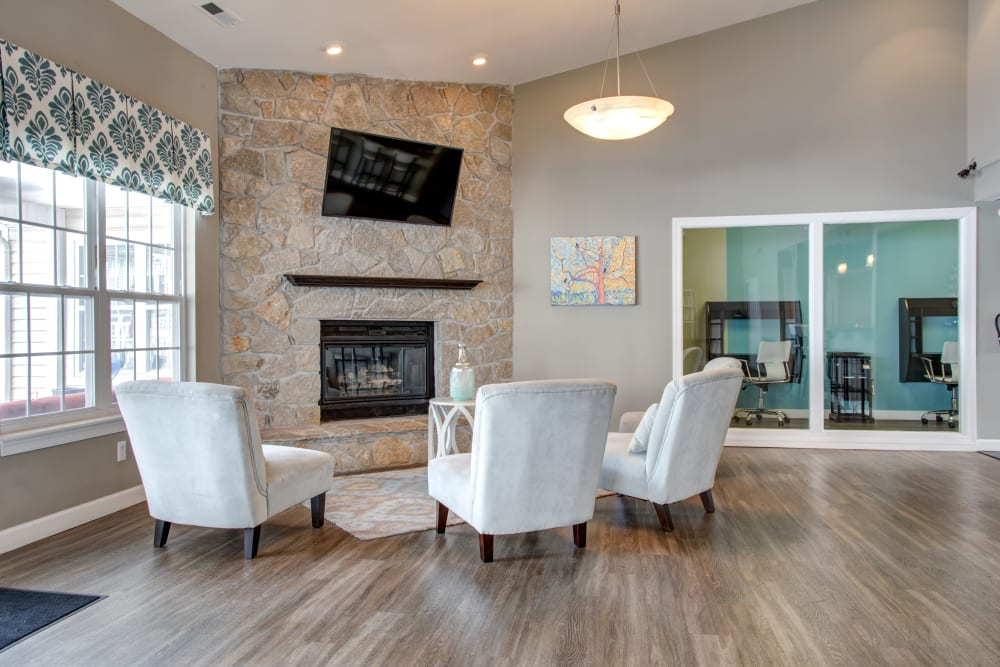 A spacious clubhouse with a fireplace and comfortable seating at Greenway Chase in Florissant, Missouri