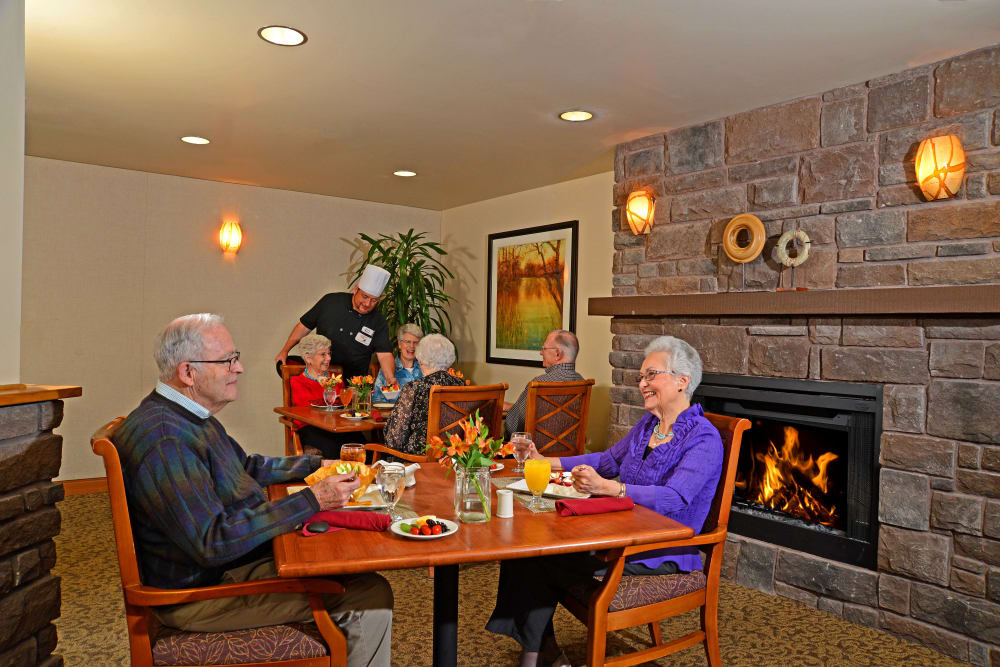 Residents sitting by a fireplace eating at Quail Park at Browns Point in Tacoma, Washington