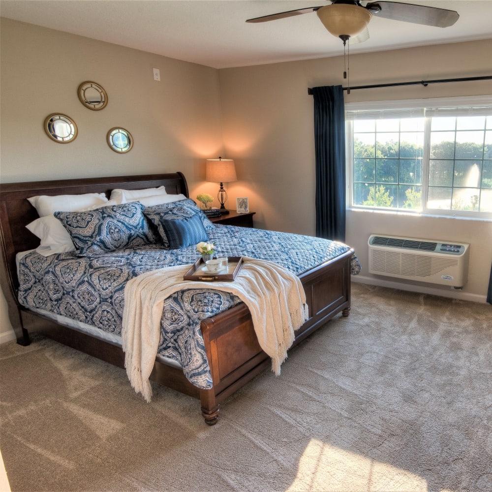 Model resident bedroom with a large window at Inspired Living Sugar Land in Sugar Land, Texas.