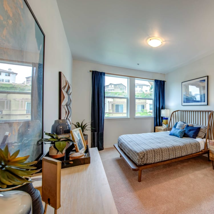 Model home's bedroom with plush carpeting and draped window at Sofi at Topanga Canyon in Chatsworth, California