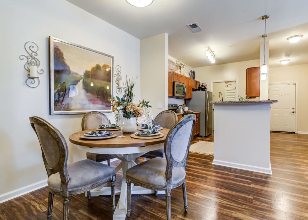 Cozy dining room with wood-style flooring in a model home at Commonwealth at 31 in Spring Hill, Tennessee