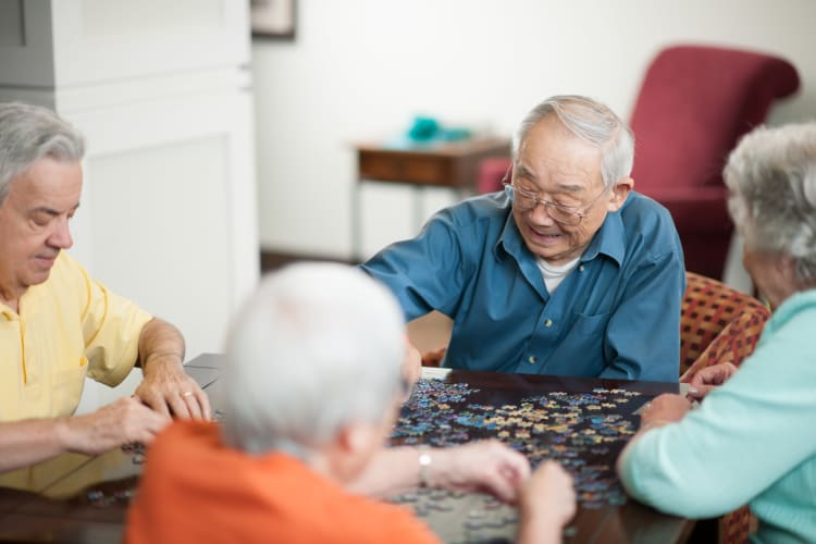 A group of residents putting together a puzzle at Harmony at Independence in Virginia Beach, Virginia