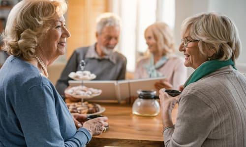 Resident friends having tea at Merrill Gardens.