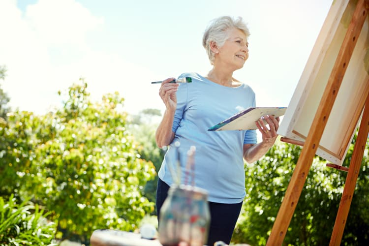 A smiling resident painting outside at Harmony Senior Services in Charleston, South Carolina