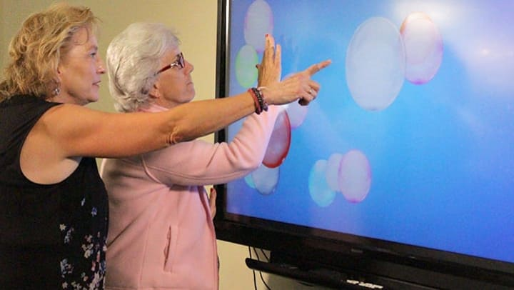 Arbors staff member utilizing touch-screen technology, iN2L, with resident.
