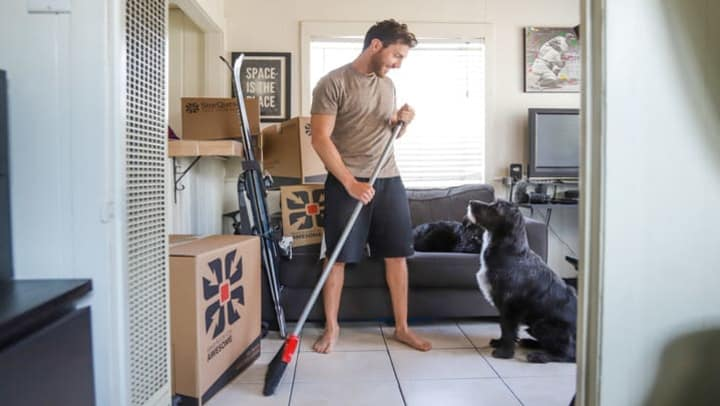 man cleaning house with broom next to dog