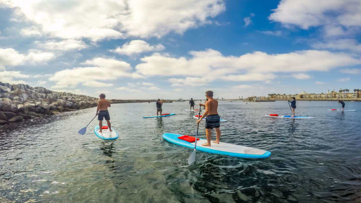 group of friends stand-up paddle boarding in a large body of water