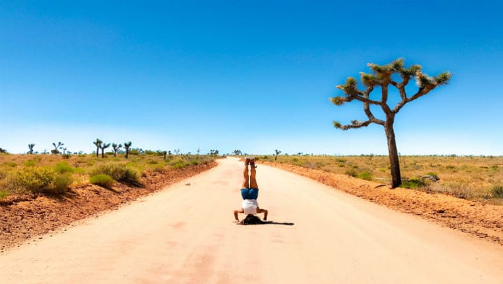 woman doing a headstand on dirt road in desert setting