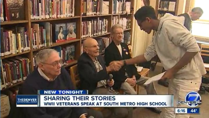 student shaking hands with WWII vet