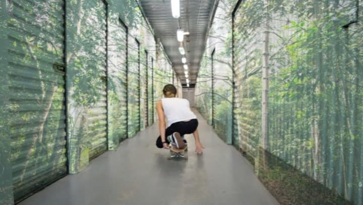 young woman crouching on skateboard riding through a row of tree-painted self storage units