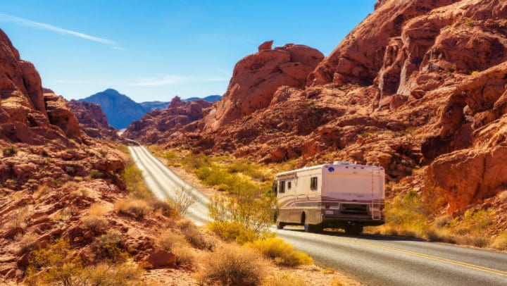 RV driving through scenic desert landscape