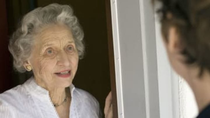 An elderly woman answering the front door