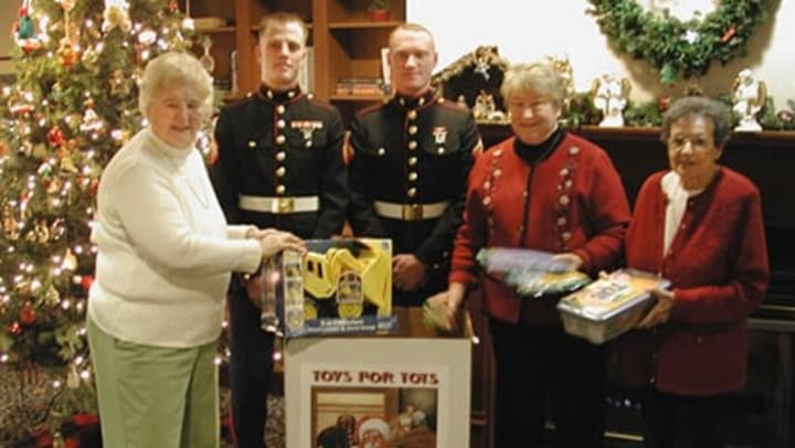 Residents and military members with toys for tots