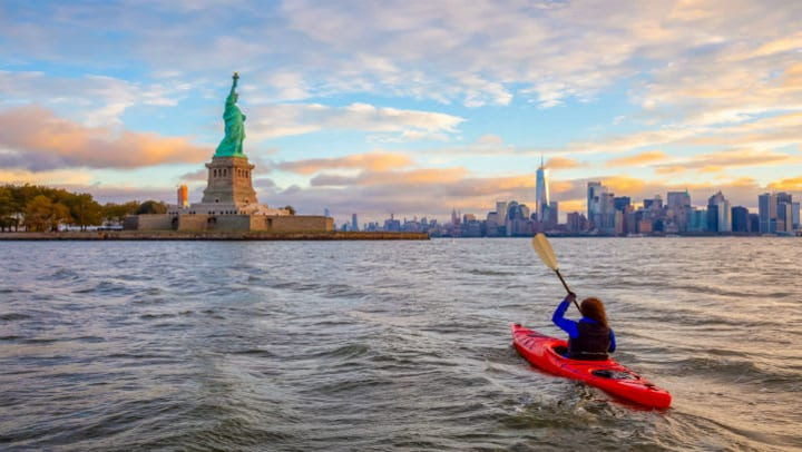 Woman kayaking Hudson River toward the Statue of Liberty