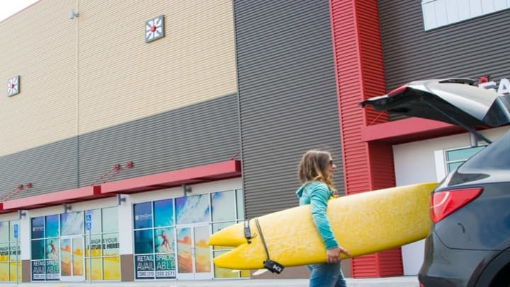 woman holding yellow surfboard by car at StorQuest self storage location