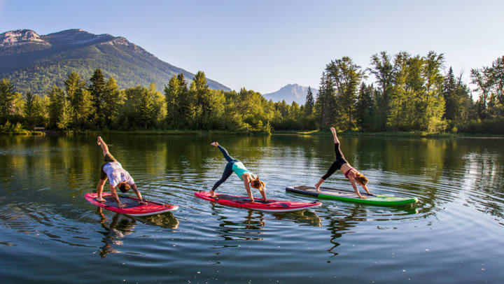 three women perform yoga on a paddle board in the middle of a lake