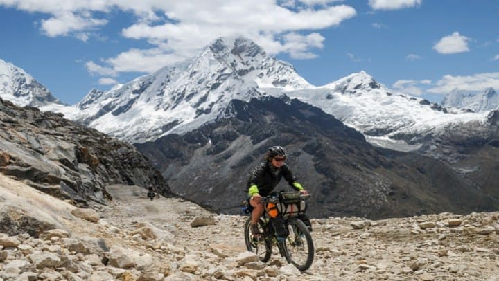 woman on bike with mountains in the background