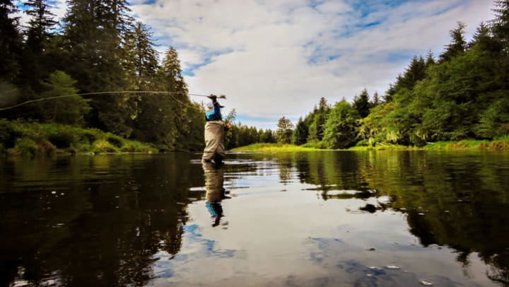 man standing in river casting a fly fishing reel