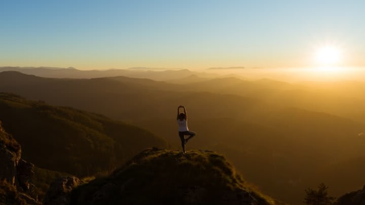 woman doing yoga move on mountain top over looking valley below during sunrise