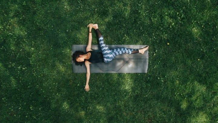 Woman on yoga mat in grass practicing yoga near Olympus Carrington