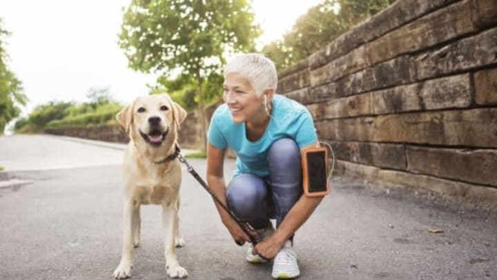 Older woman with headphones on bending at the knee and smiling at her dog