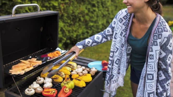 Woman holding a spatula over vegetables on a barbecue grill while smiling.