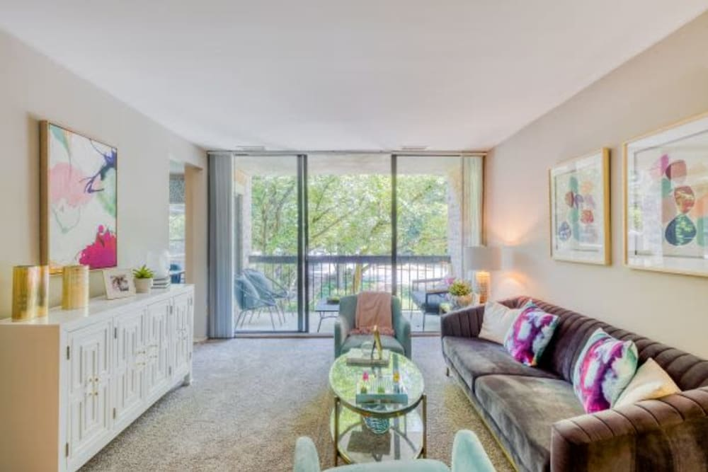 Model Living room with floor to ceiling windows at The Timbers at Long Reach Apartments in Columbia , Maryland
