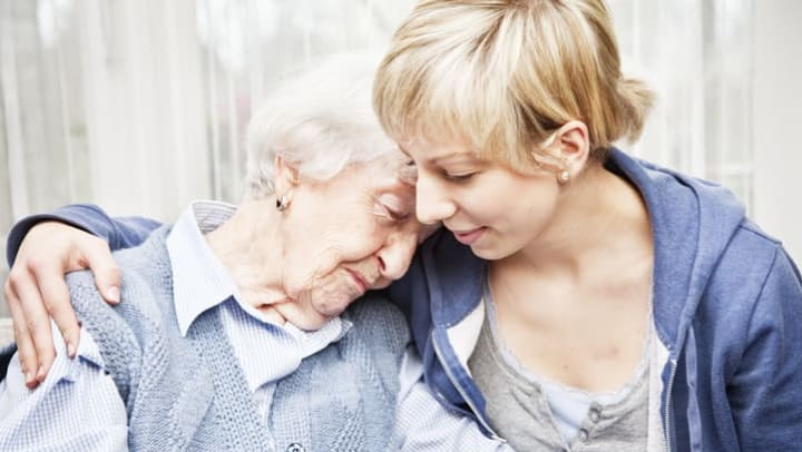 Younger woman consoling senior woman at {{location_name}} in {{location_city}}, {{location_state_name}}