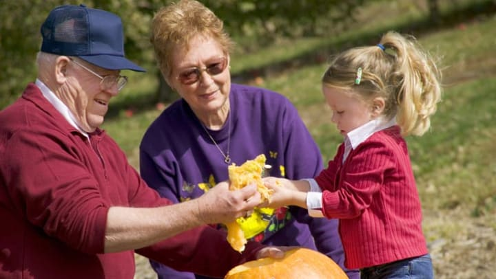 Grandparents and their grandchild carving pumpkins together outside