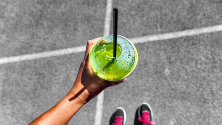 Resident drinking a green smoothie near Olympus Waterford in Keller, Texas