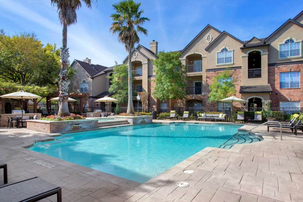 Resort-inspired swimming pool with expansive sundeck and waterfall at Regency at First Colony in Sugar Land, Texas