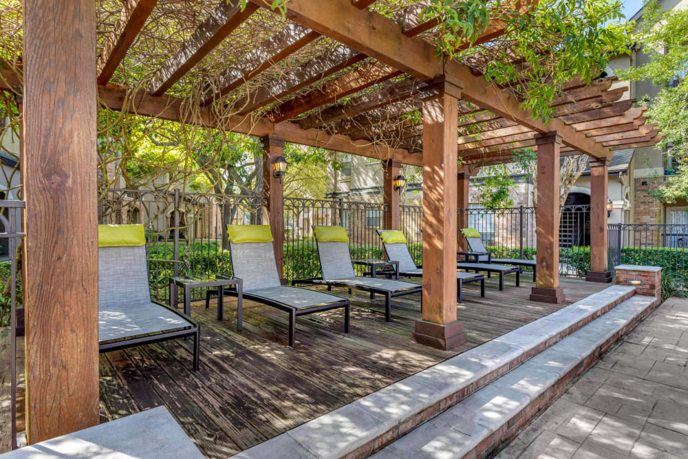 Shaded lounge chairs under a wooden pergola in the courtyard at Regency at First Colony in Sugar Land, Texas