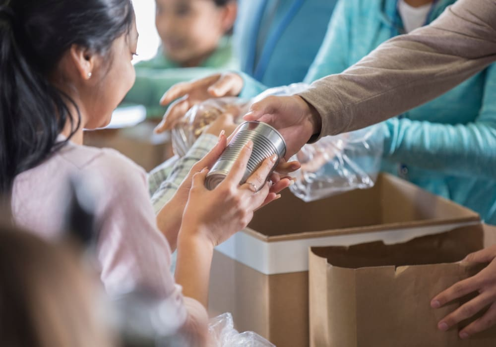 Employee volunteers handing out food to children in need at a food bank near American Capital Group in Bellevue, Washington